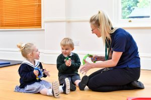 early years foundation stage children learning through play with teacher