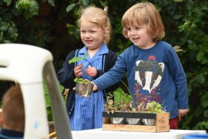 starting nursery children playing outdoors with plants