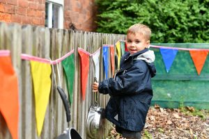 Nursery FAQ child outside playing with bunting