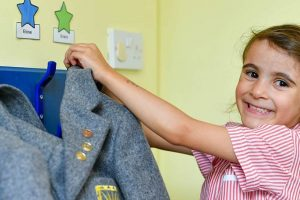 nursery admissions in Worcestershire child hanging blazer up on peg