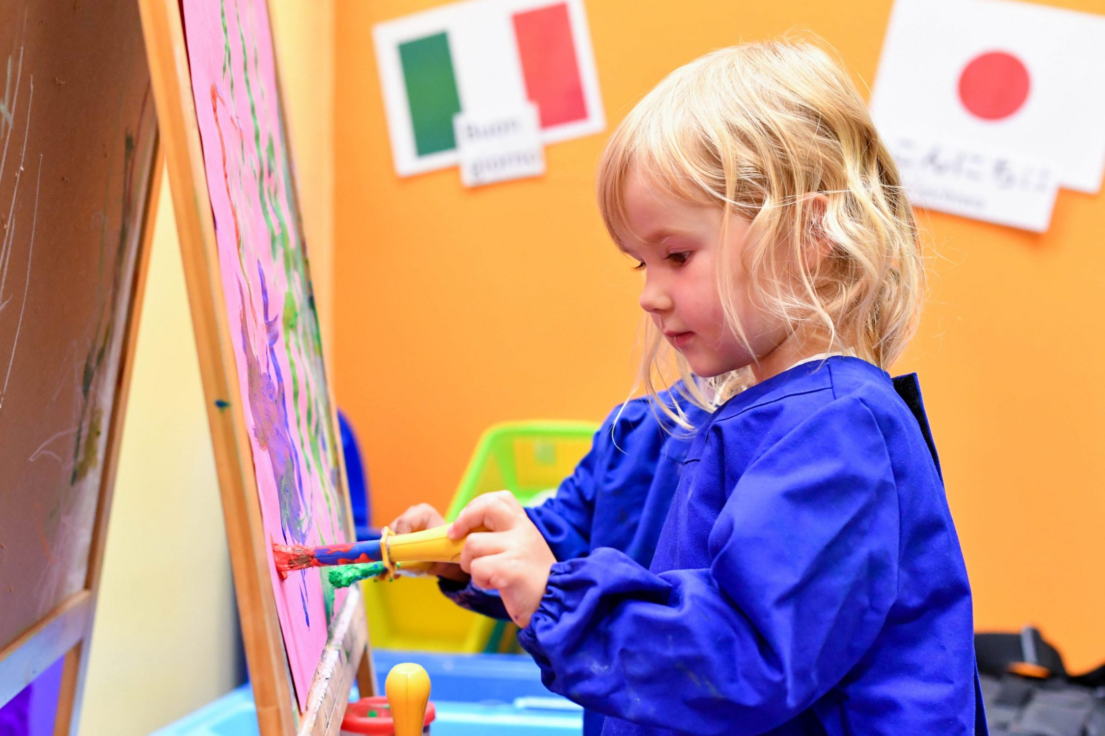 Child in classroom painting with paintbrush and easel