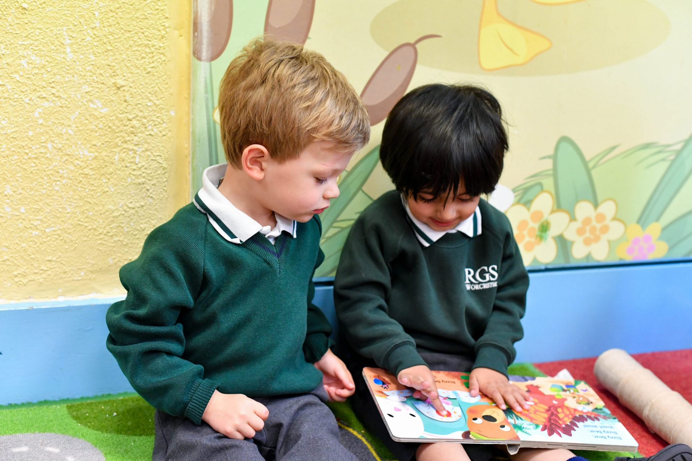 Early years children sat together reading a book