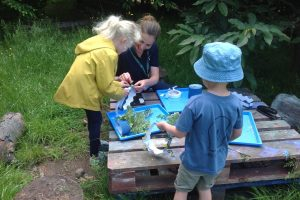 Forest School children making artworks outdoors with teacher