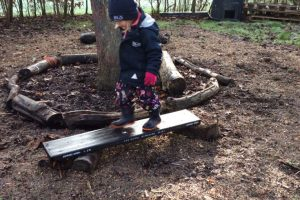 Forest School child exploring outdoors by tree