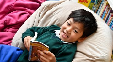 Child with book on beanbag reading in library