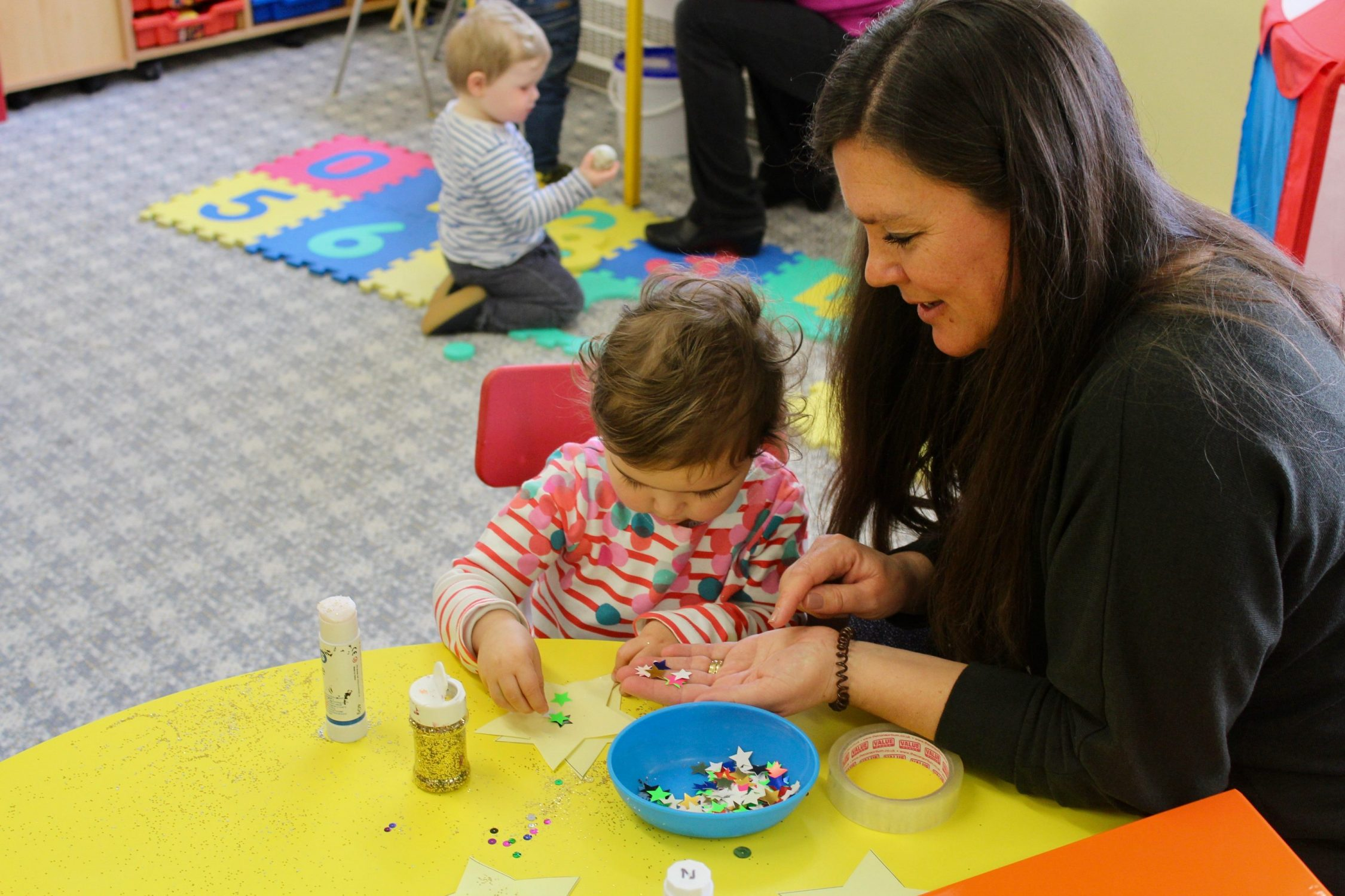 Nursery child and key person playing craft activity together