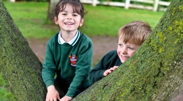 Forest School pupils outdoors by tree