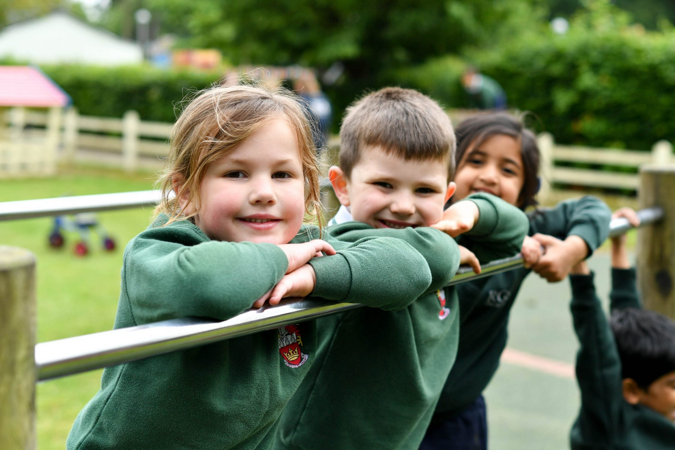 Reception pupils outdoors smiling in uniforms leaning on post