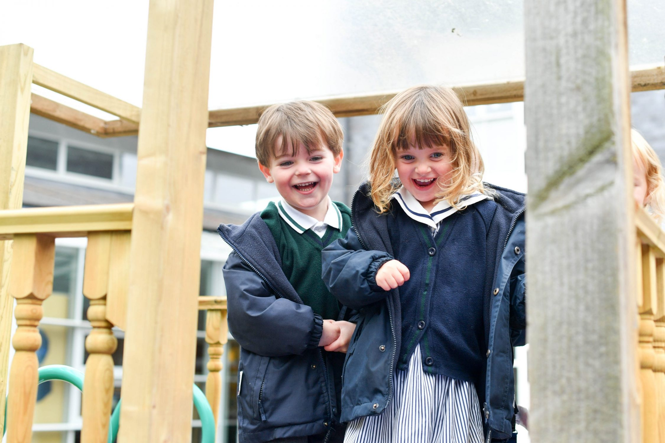 Children playing outdoors together on play area laughing